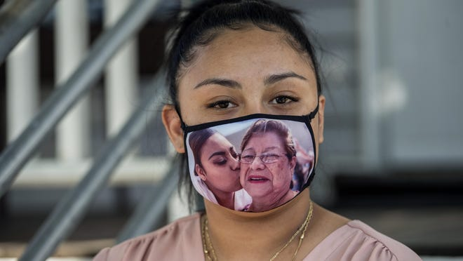Framingham High class of 2020 graduate Anahi Famania with the mask she wore to graduation ceremonies to honor her grandmother, Alicia Delcarmen Contreras, who died of COVID complications in May.