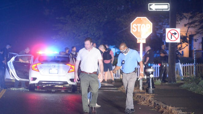 Police look for evidence, including shell casings, after a woman was shot in a drive-by shooting in a Honda Civic car near 74 Belair St. in Brockton, Wednesday, Sept. 2, 2020. The victim, who suffered non-life-threatening injuries, was taken by ambulance to Good Samaritan Medical Center in Brockton.
