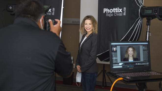 Photographer Sanjeev Singhal takes a photo of Emily Dowdell at Augusta Mall as part of 10,000 Headshots, an effort organized by photographers from around the country to provide complimentary professional headshots for unemployed workers. MICHAEL HOLAHAN/THE AUGUSTA CHRONICLE]