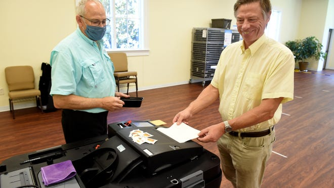 Voter Sergei Kirov, right, loads his paper ballot into the scanner with the help of poll worker Don Hoercher during after voting at Christ Church Presbyterian in Evans, Ga., Tuesday afternoon June 9, 2020.