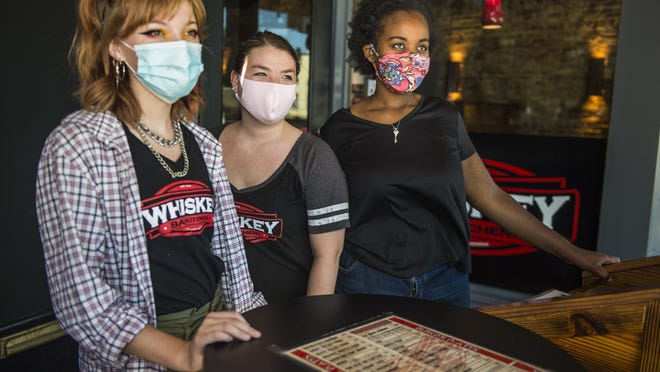 Whiskey Bar Kitchen associates, from left, Riley Morrison, Lindsay Minnick and Genesia Brown wait outside for the lunch crowd to arrive at the restaurant on Broad Street in Augusta, Ga., Monday morning July 13, 2020.