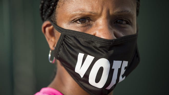"Caprice Clipps wears a ""vote"" mask as she waits to early vote in the 2020 general election."