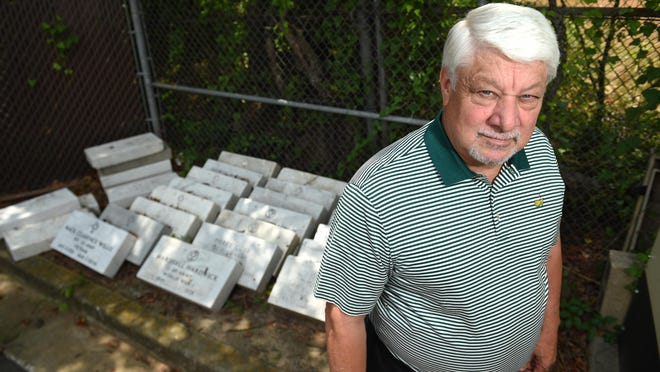 Richmond County Coroner Mark Bowen with some of the left-over military grave markers stored at the coroner's facility in Augusta, Ga., Thursday afternoon June 11, 2020.