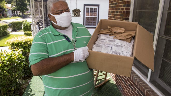 Rev. Larry Fryer holds a box of masks that he plans on giving away.  Photographed in Augusta, Ga., Thursday morning August 26, 2020.