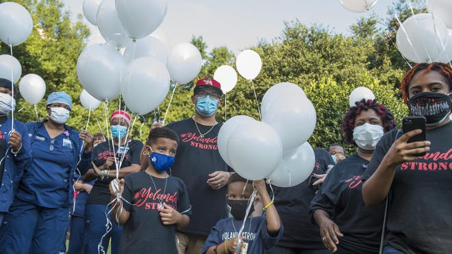 Nurse Yolanda Coar's family, including her husband, Matthew Coar (center) and sons Evan (center left) and Maddox (center right), wait to release balloons in her memory Aug. 20 outside AU Medical Center.