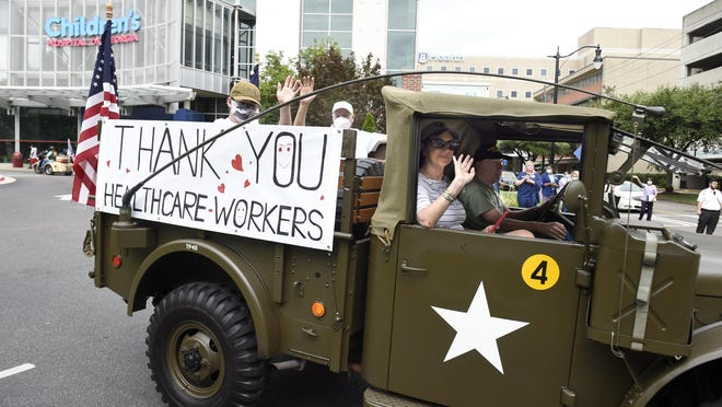 People wave from an old military vehicle during the parade to support healthcare workers near the Children's Hospital of Georgia in Augusta, Ga., Monday morning July 6, 2020.