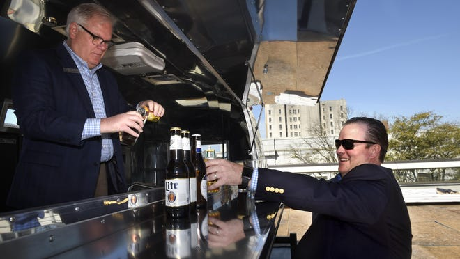Edgar's Hospitality Group's Tim Ligon, left, and Trip Harrison open a couple celebratory beers after a crane hoisted an Airstream Travel Trailer up to the third-floor of Augusta University tower, at 699 Broad Street, to become part of downtown's newest outdoor space - Edgar's Above Broad in Augusta, Ga., Monday morning March 9, 2020.   Edgar's Above Broad is expected to open later this spring and will be a rooftop bar and dining spot. The Airstream sits on the large outdoor terrace and will house a bartender for visiting  guests.