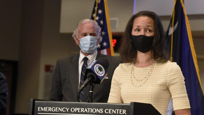 FIle - South Carolina Gov. Henry McMaster, left, looks on as state epidemiologist Linda Bell, right, speaks during a COVID-19 briefing on Wednesday, July 29, 2020, in West Columbia, S.C. As of Monday, McMaster says all businesses will be allowed to be open, as long as they adhere to social distancing and capacity limits.