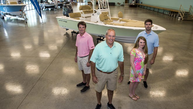 David Whyte, middle, owner of his family business, Augusta Marine, with his son John-Christian Whyte, from left, daughter Callie Lovering and son-in-law Jon Michael Lovering in the largely empty showroom at Augusta Marine in Augusta, Ga., Thursday morning, August 6, 2020.