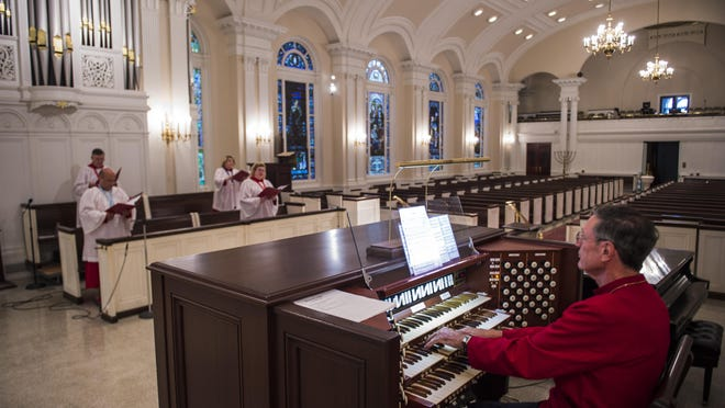 Keith Shafer, director of music, plays the organ as choir members sing during a recording session at Saint Paul's Church on Wednesday evening.