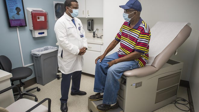 Dr. Germame Ajebo talks with colon cancer patient Tommy Denson at the Georgia Cancer Center in Augusta, Ga., Thursday afternoon September 3, 2020.