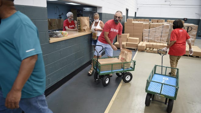 FILE - Volunteers, like Marc Husid, middle, load up wagons with food then roll them out the the recipient's car at the Dream Center in Augusta, Ga., Tuesday morning July 14, 2020.
