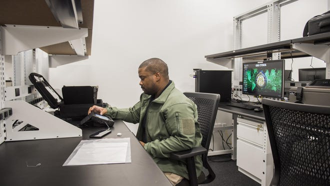 GBI special agent Wendell Goodman works on breaking into a cell phone at the GBI offices at the Georgia Cyber Center in Augusta.