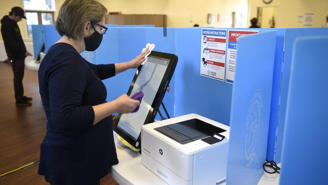 Election official Rosemary Del Toro sanitizes a voting machine at Christ Church, Presbyterian in Evans, Ga., Tuesday morning November 3, 2020.