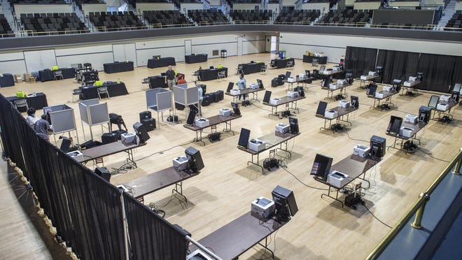 Workers set up voting machines Oct. 8 at the Bell Auditorium in preparation for advance voting in the Nov. 3 general election.