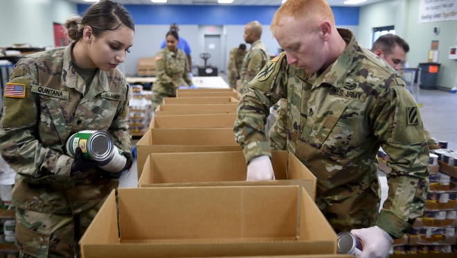 Georgia National Guard Spc. Jennifer Quintana, left, and Staff Sgt. Christopher Powell  pack boxes of food at Gold Harvest Food Bank in Augusta, Ga., Monday afternoon March 30, 2020.