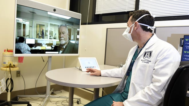 FILE - During a telemedicine demonstration, Dr. Matt Lyon, right, Augusta University Emergency Medicine Professor, talks with medical personnel on screen in Washington, Ga., from an office at the Augusta University Medical Center in Augusta, Ga., Tuesday morning September 2, 2020.
