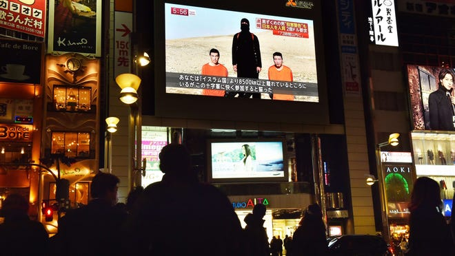 People look at a large TV screen Jan. 20, 2015, in Tokyo. The screen shows news reports about two Japanese men (in orange) who have been kidnapped by the Islamic State group. Japanese Prime Minister Shinzo Abe, speaking at a news conference during a visit to Jerusalem on Jan. 20, demanded that the Islamic State group immediately free the two Japanese hostages unharmed after the jihadists posted a video threat to kill them.