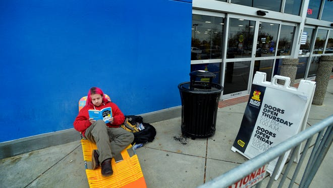 Brian McCauley was the first in line for Black Friday sales at Best Buy, where he set up a chair on Monday night to camp out for three days. Here he reads to pass the time on Tuesday, November 25, 2014.