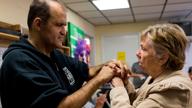 Phillip Quibodeaux, a deaf and blind patient, speaks to Paulette Gutherie using tactile sign language during an occupational therapy session at Amelia Manor Nursing Home in Lafayette.