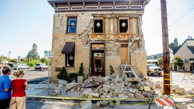 Pedestrians stop to examine a crumbling facade at the Vintner's Collective tasting room in Napa following Sunday's earthquake. Officials say 15 to 16 buildings are no longer inhabitable.<240><131><240><8,3><cutline_credit>Noah Berger/The Associated Press</cutline_credit><240><240>