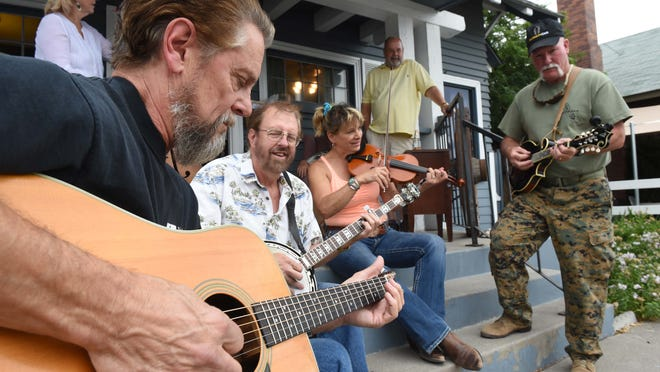 From left, Don Timmer, Rich Sparks, Renee Lauderback and Steve Gallagher play for a drop-by audience in the front yard of the Mountain Music Parlor, 735 S. Center St., on August 29.