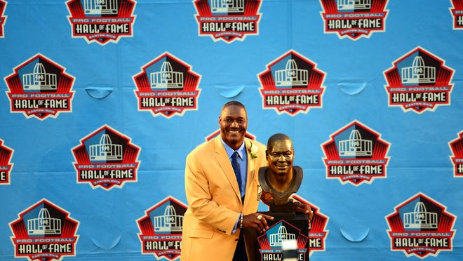 Former Tampa Bay Buccaneers linebacker Derrick Brooks poses with his bust during the 2014 Pro Football Hall of Fame Enshrinement.
