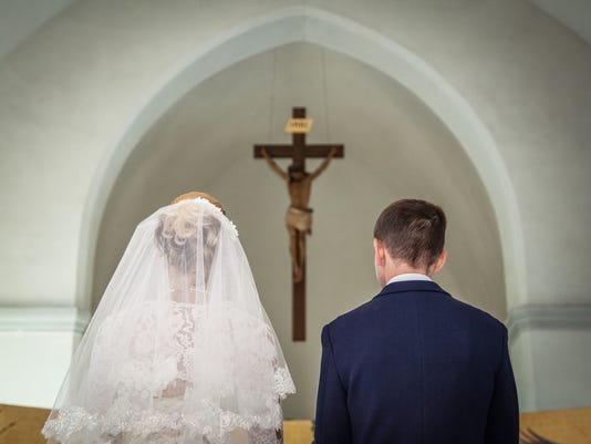 Bride and groom stand before crucifix in church 2