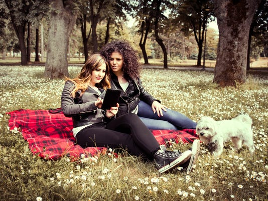 two beautiful woman and white dog look tablet in park