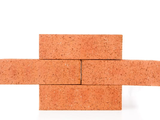 Four clay bricks building a wall