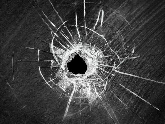 Bullet shot cracked hole on broken window glass