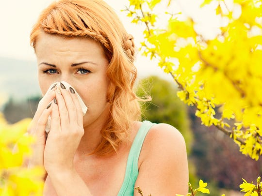 Young woman sneezing among flowers outdoors.