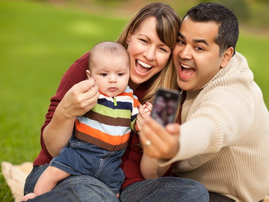 Happy Mixed Race Parents and Baby Boy Taking Self Portraits