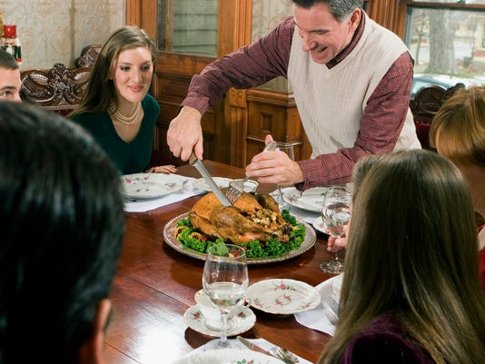 Mature man carving roast turkey with family