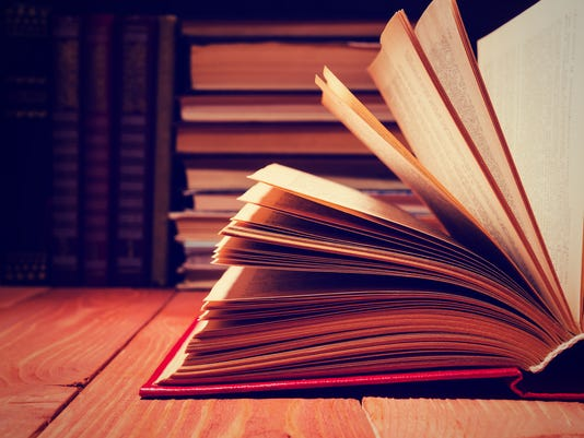 Book opened in library on wooden shelf. Education background with