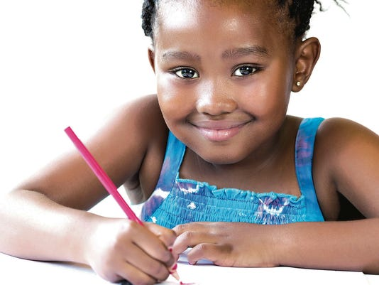 African youngster holding red pencil.