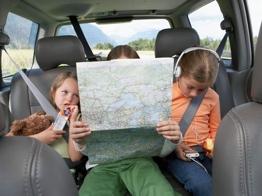 Three girls (6-8 years) sitting on rear seat of car on road trip