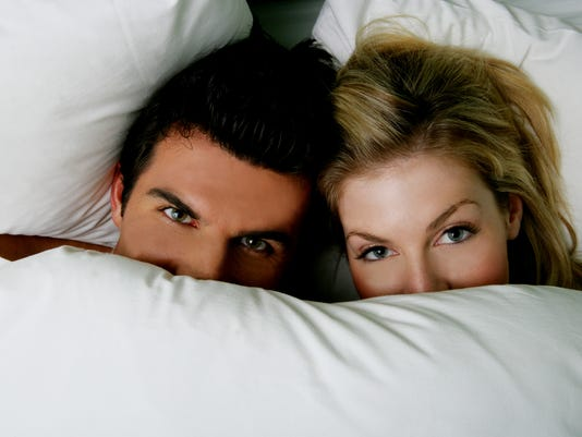 Young couple under the covers in bed.