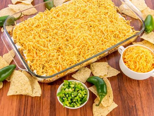 preparation of layered bean dip with jalapenos, sour