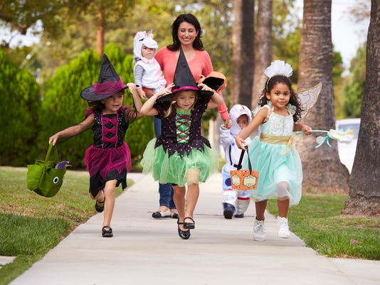 Parent Taking Children Trick Or Treating At Halloween