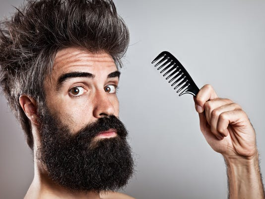 Messy haired bearded man holding a comb looking at came
