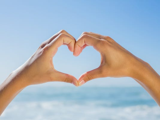 Female hands making heart shape by the sea