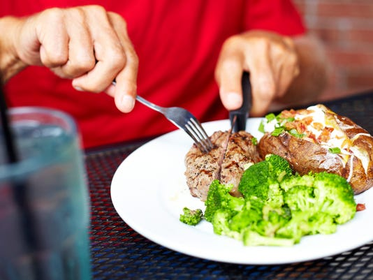 Senior Man Eating Strip Steak At Restaurant Table
