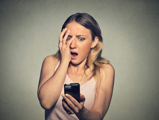 anxious scared girl looking at phone seeing bad news