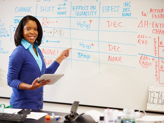 Science teacher at whiteboard with digital tablet