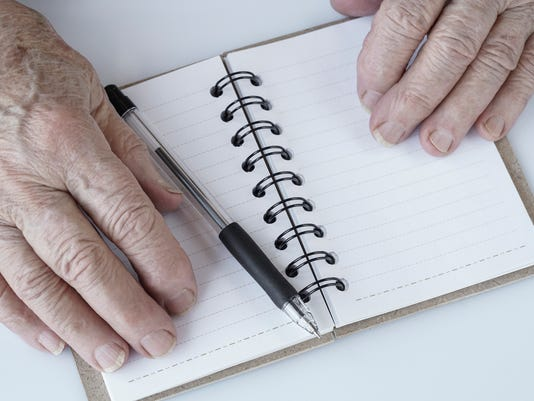 Wrinkled hands on an empty notebook