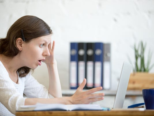 Young shocked business woman looking at laptop computer