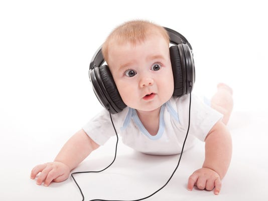 smiling naked baby with headphones on a white background