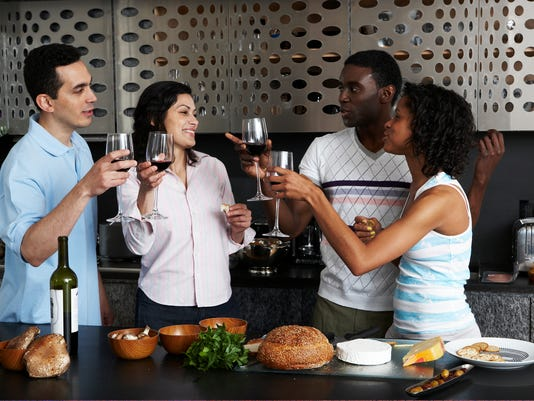 Drinking wine while preparing meal in kitchen