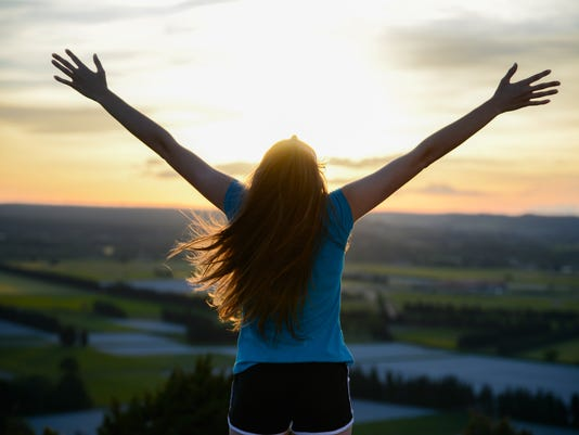 happy young woman outdoor rising hands looking landscape on sunset